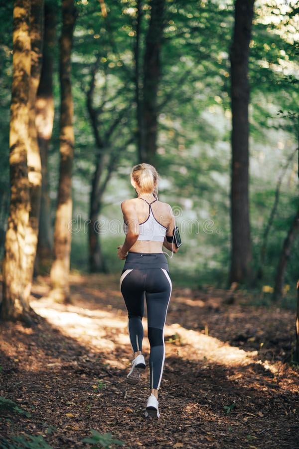 Fitness sport woman running on the road in the morning, Sun light flare stock photos