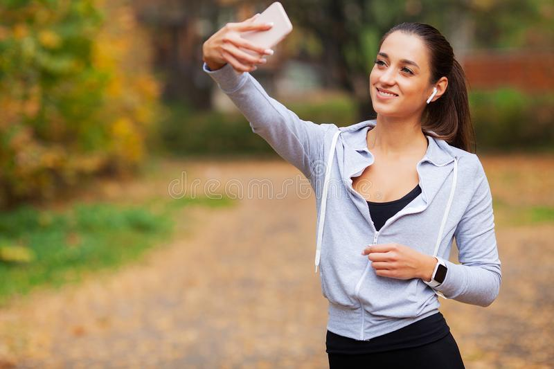Fitness. Sport woman taking selfie photo on mobile phone in summer park.  stock image