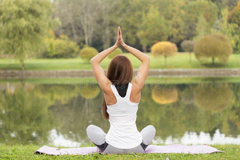 Fitness, sport, yoga en gezond levensstijlconcept - het jonge aantrekkelijke vrouw mediteren in lotusbloem stelt op rivier of mee royalty-vrije stock foto's