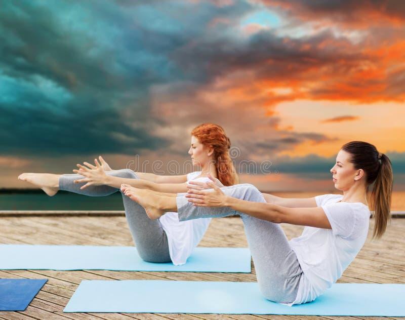 Women making yoga in half-boat pose outdoors stock image