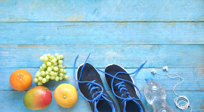 Fitness, sports and reducing weight for the springtime, pair of runners and fruit,free copy space, stock photo