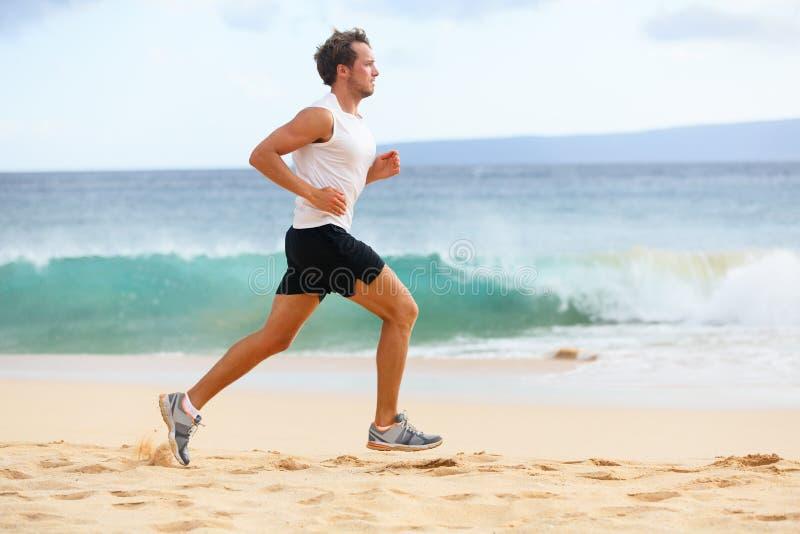 Fitness sports runner man jogging on beach royalty free stock photos