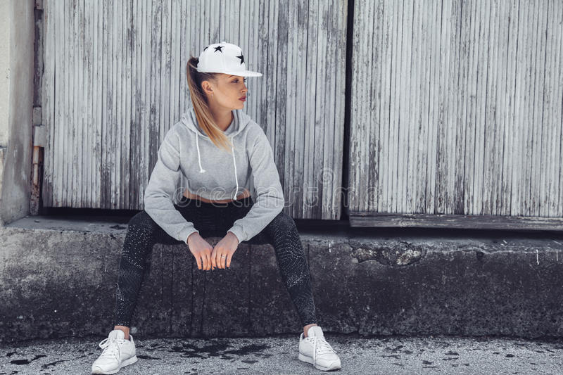 Fitness sporty girl wearing fashion clothes. Fitness sporty girl wearing fashion sportswear over street wall, outdoor sports, urban style. Teen model in swag royalty free stock images