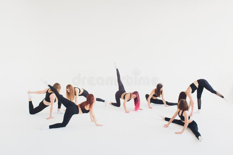 Fitness, stretching practice, group of two attractive happy smiling fit mature women working out in sports club, doing. Extended Side Angle posture, utthita stock photo