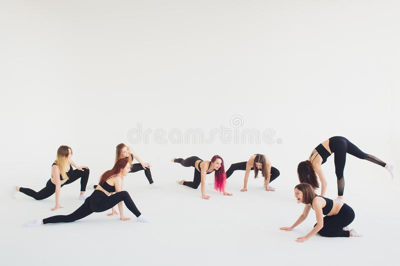 Fitness, stretching practice, group of two attractive happy smiling fit mature women working out in sports club, doing. Extended Side Angle posture, utthita royalty free stock image