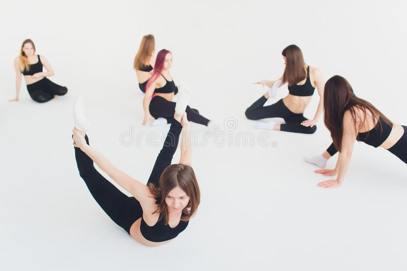 Fitness, stretching practice, group of two attractive happy smiling fit mature women working out in sports club, doing. Extended Side Angle posture, utthita stock photos