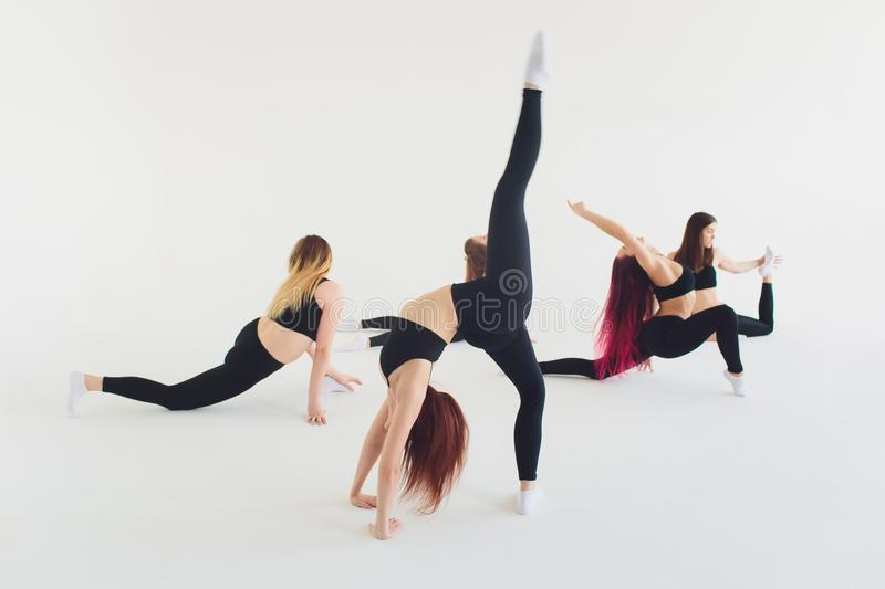 Fitness, stretching practice, group of two attractive happy smiling fit mature women working out in sports club, doing. Extended Side Angle posture, utthita royalty free stock photos