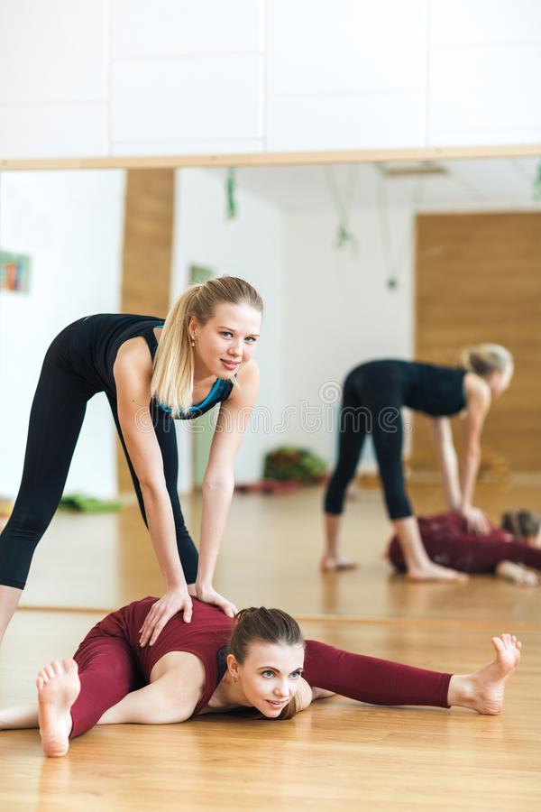 Fitness, stretching practice, yoga teacher with student working out in sports club, instructor helping female student to do asana royalty free stock photography