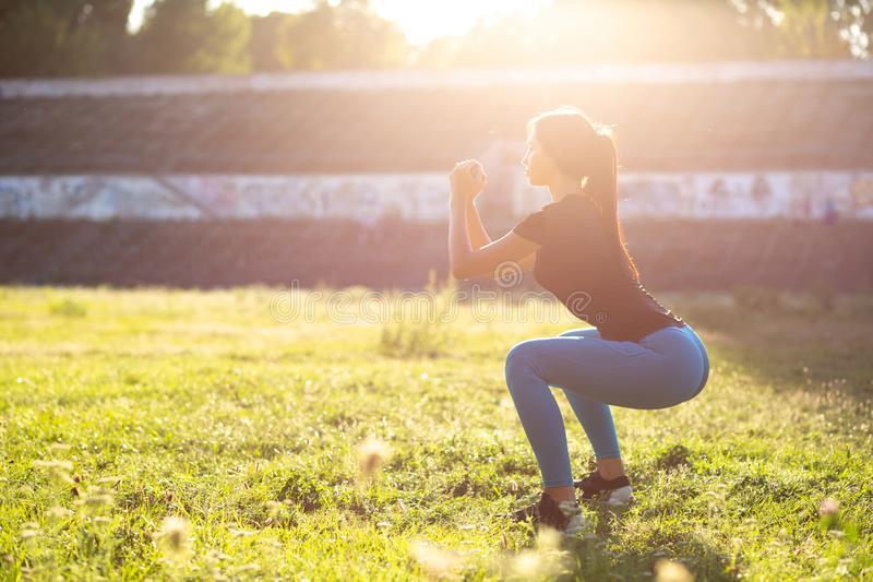 Fitness tanned girl in sport clothes crouching at the stadium in. Fitness tanned woman in sport clothes crouching at the stadium in rays of sun. Empty space stock images