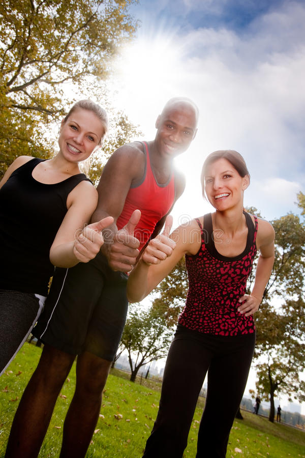 Fitness Thumb Up. A happy group of people in the park exercising stock photography