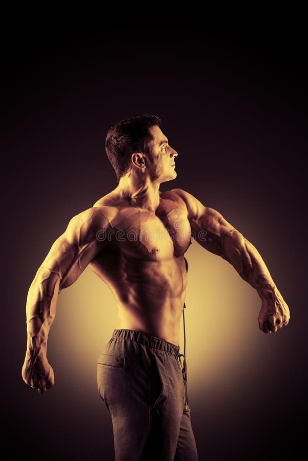 Fitness time. Handsome muscular bodybuilder posing over black background stock images