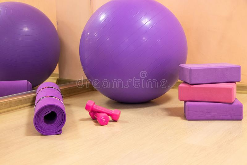 Fitness tools - ball, pink and purple cubes and dumbbells, purple mat, sports concept. Horizontal photo royalty free stock images