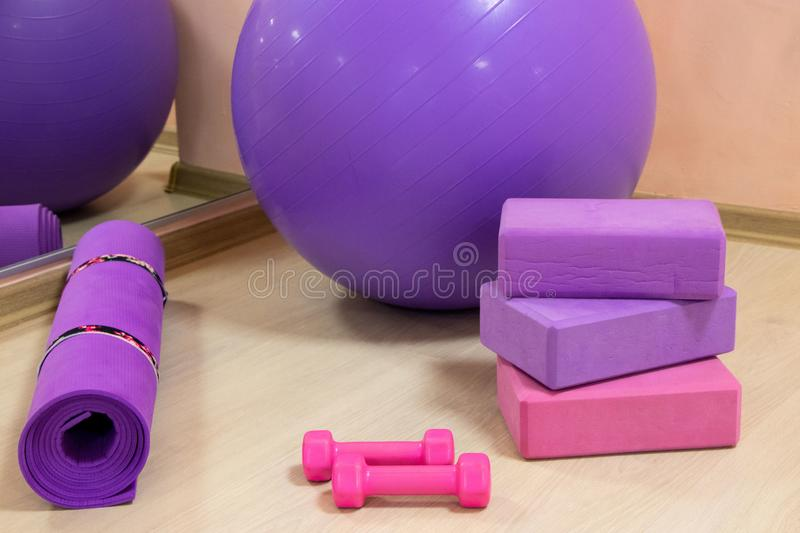 Fitness tools - ball, pink and purple cubes and dumbbells, purple mat, sports concept. Horizontal photo stock images