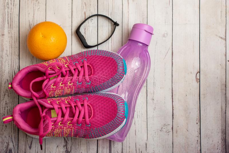 Fitness tracker, orange, water bottle and pink sneakers on light wooden table with copy space. Top view. Fitness tracker, orange, water bottle and pink sneakers royalty free stock image