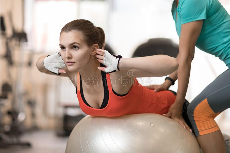 Fitness trainer helping young girl doing back exercises in gym royalty free stock photography