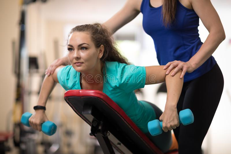 Fitness trainer helping young woman doing exercises in gym stock photos