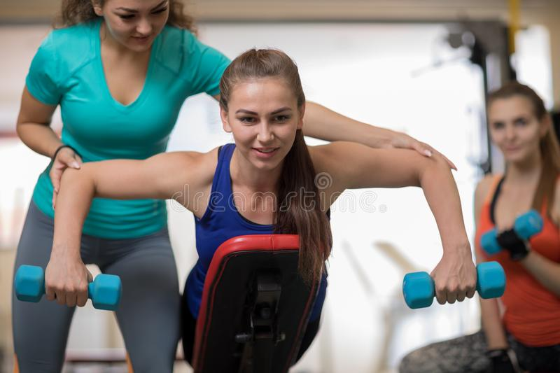 Fitness trainer helping young woman doing exercises in gym royalty free stock photography