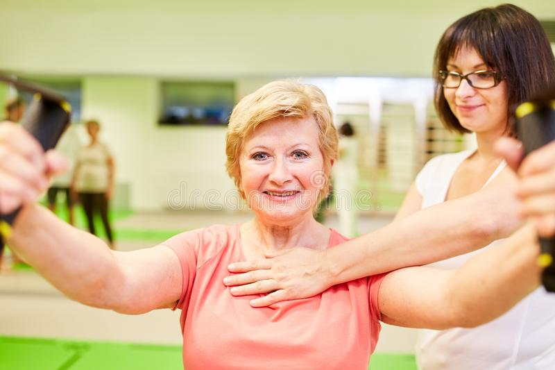 Fitness trainer helps senior woman with sling training royalty free stock photography