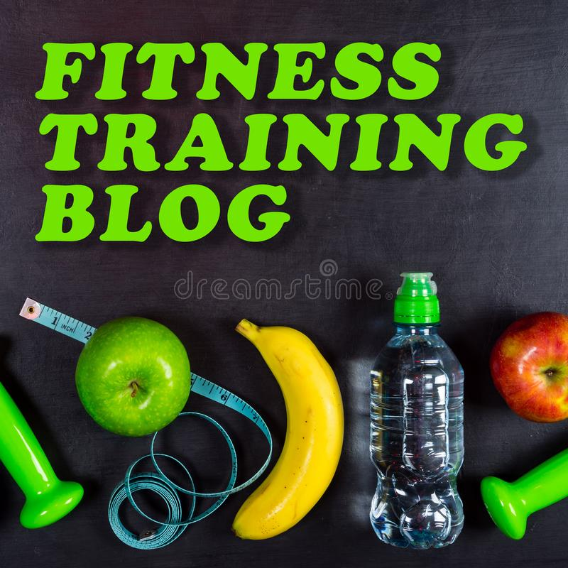 Fitness training blog concept. Dumbbell, massage ball, apples, banana, water bottle and measuring tape on black background royalty free stock image