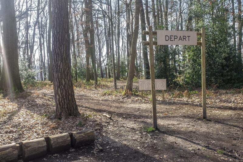 Fitness training in forest. Sign planted in a forest that indicates `Depart, Start`. Fitness training in forest. Sign planted in a forest that indicates Depart stock images