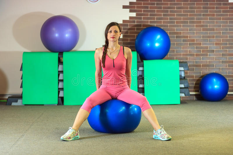 Fitness training. Young beautiful white girl in a pink sports suit does physical exercises with a blue fit ball. Young beautiful white girl in a pink sports royalty free stock image