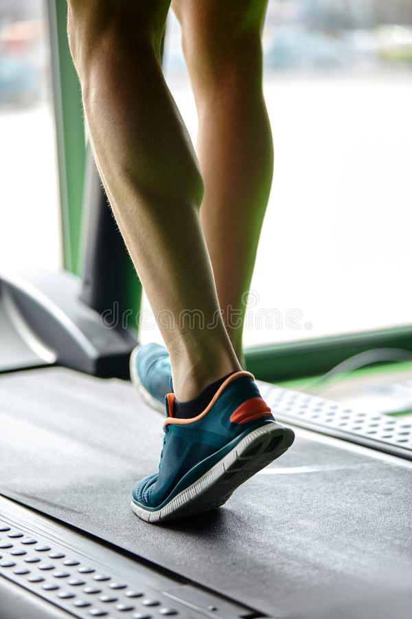 Fitness treadmill. Man running in a modern gym on a treadmill concept for exercising, fitness and healthy lifestyle royalty free stock photography