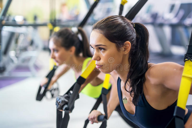 Fitness trx suspension straps training exercises. Women doing push-ups, working with own weith at gym royalty free stock image