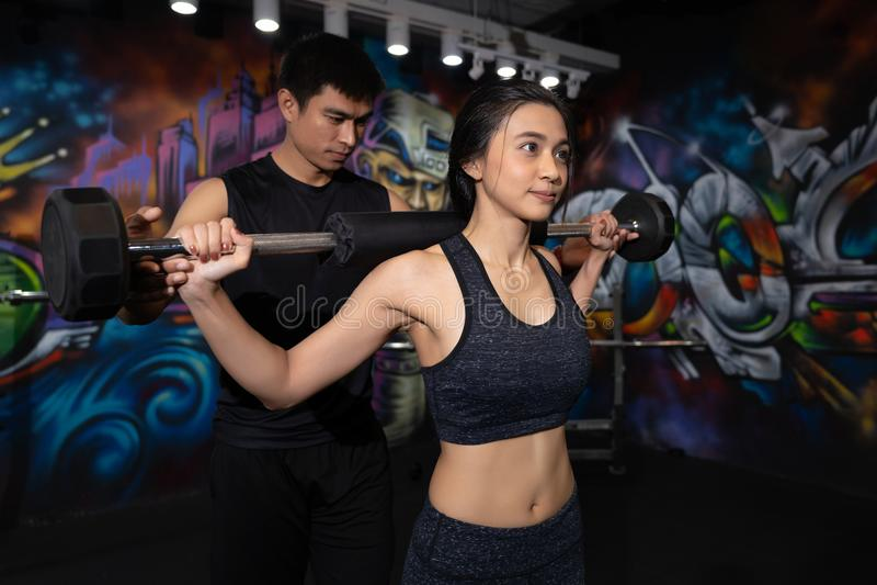 Fitness vrouw het opheffen gewicht, Sport, het bodybuilding, levensstijl en mensenconcept - Jonge man en vrouw met de spieren van royalty-vrije stock fotografie