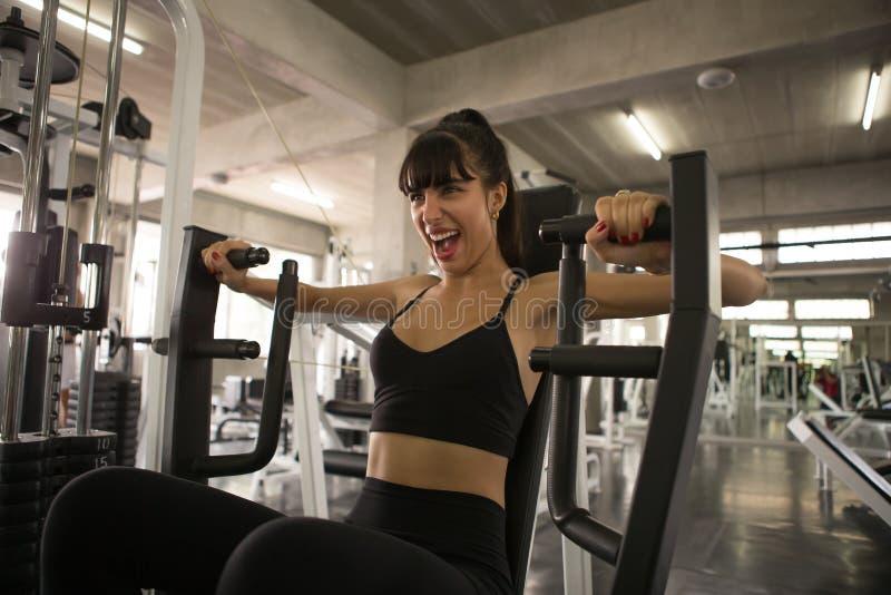 fitness vrouw in sportkleding die de Borst van de bouwspieren, bicepsen, wapen met duwmachine uitoefenen in sportgymnastiek train stock foto's