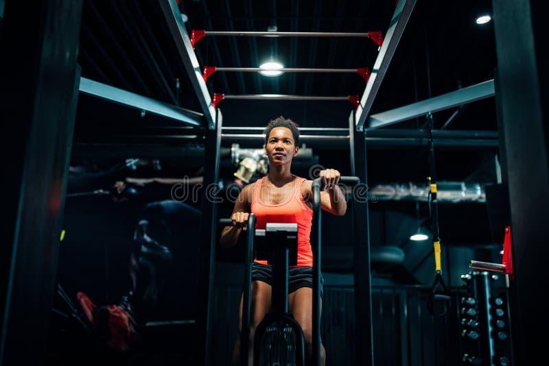 Fitness-Weibchen, die mit dem Luftfahrrad trainieren, im Fitnessstudio 'Crossfit' stockfotos