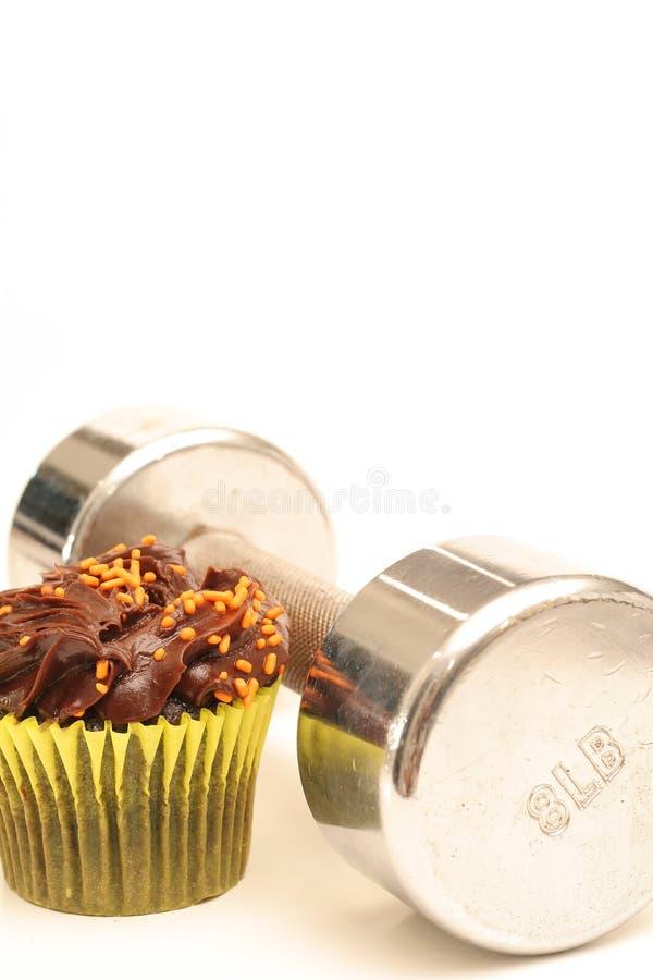Fitness weight & chocolate cupcake vertical stock photo