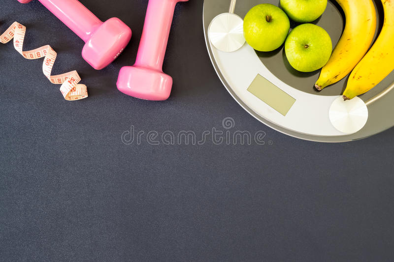 Fitness and weight loss concept, dumbbells, tape measure, apple stock image
