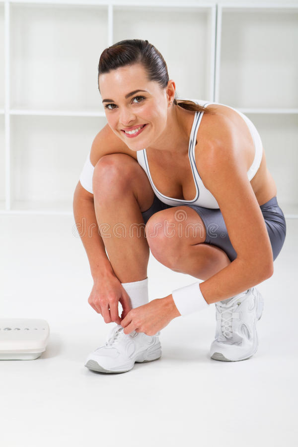 Fitness woman. A portrait of a pretty fitness woman in gym clothes tying her shoes indoors stock images