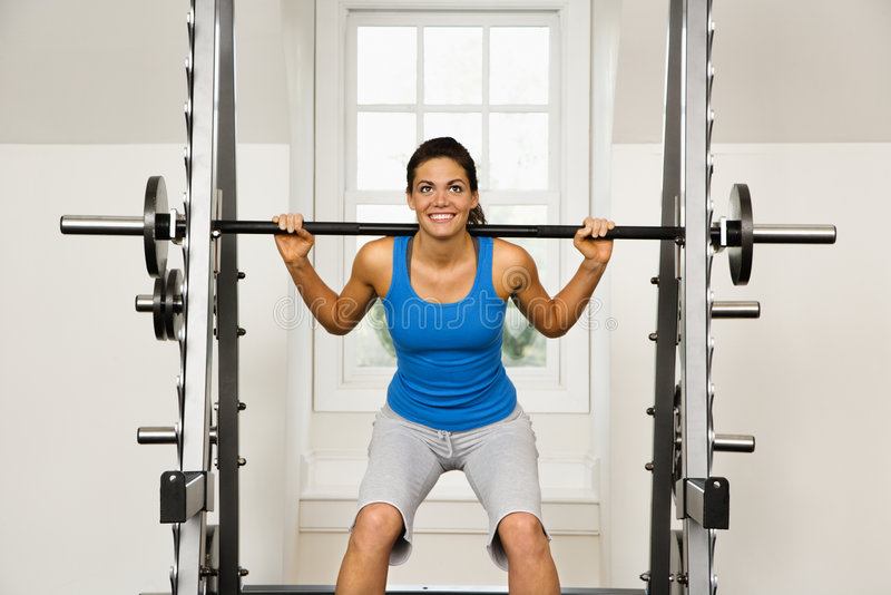 Fitness woman. Woman lifting weights in gym smiling royalty free stock photos