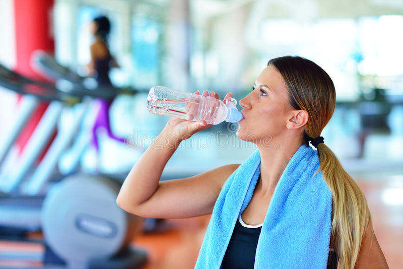 Fitness woman beautiful young girl in the gym drinking water beautiful young girl in the gym drinking water with blue towel sciox Choice Image
