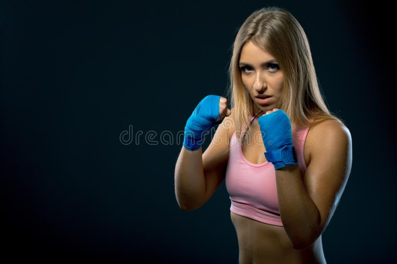 Fitness woman with the blue boxing bandages, studio shot. Over black background stock photos