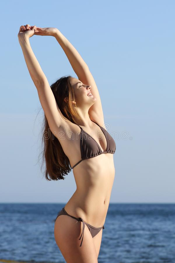 Fitness woman body posing standing on the beach. With the sea in the background stock photo