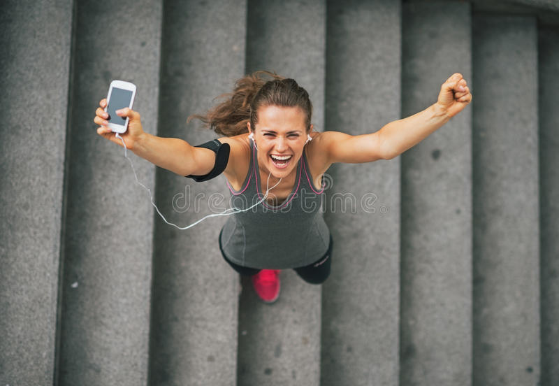 Fitness woman with cell phone outdoors in the city royalty free stock photo