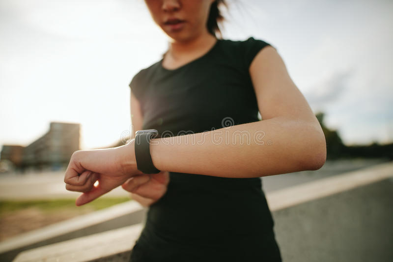 Fitness woman checking her performance on smartwatch. Close up shot of young woman runner using smartwatch outdoors. Fitness female checking her performance stock photography