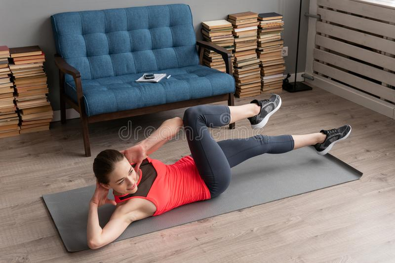 Fitness woman doing bicycle crunch exercise on mat at home royalty free stock photos