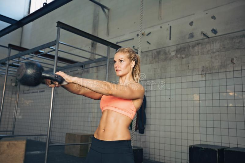 Fitness woman doing crossfit exercise. Fitness woman swinging kettle bell at gym. Young caucasian woman doing swing exercise with a kettlebell as a routine of a royalty free stock images