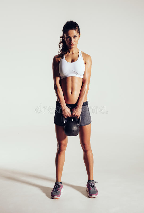 Fitness woman doing crossfit exercising with kettle bell. Beautiful fitness instructor on grey background. Female model with muscular fit and slim body royalty free stock photos