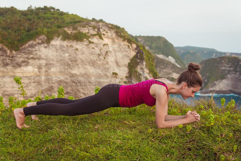 Fitness woman doing elbow plank pose on cliff near ocean. stock images