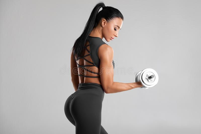 Fitness woman doing exercise for biceps on gray background. Muscular woman workout with dumbbells royalty free stock photography