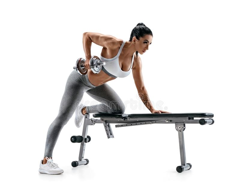 Fitness woman doing exercise with dumbbell leaning on sports bench royalty free stock photos