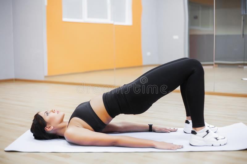 Fitness woman doing exercises on the press top view. Cute girl workout in the gym stock photography