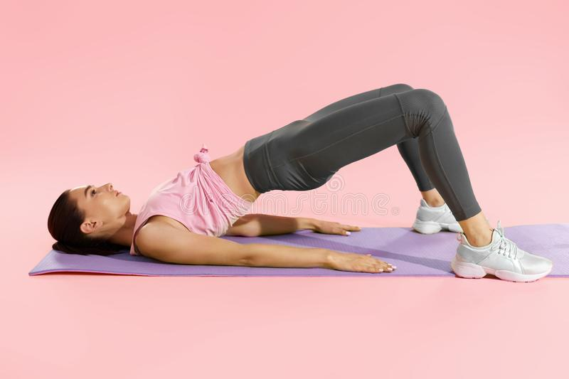 Fitness woman doing hip workout exercise on yoga mat at studio stock photography