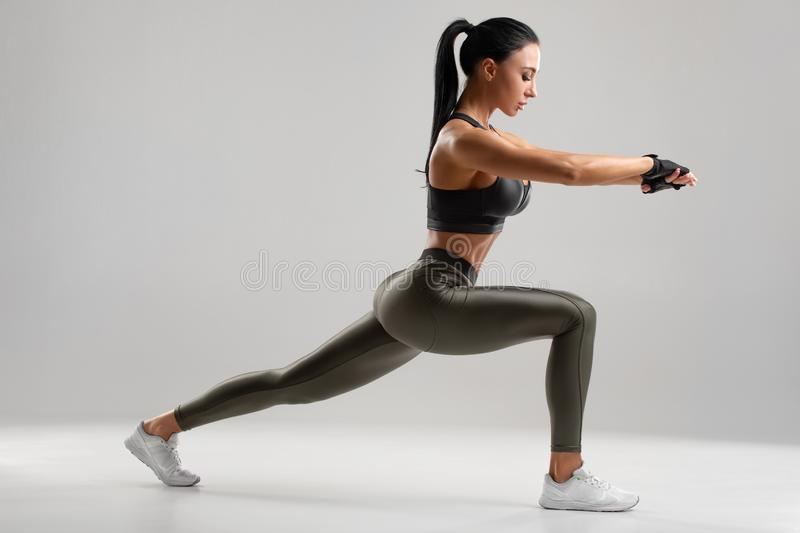 Fitness woman doing lunges exercises for leg muscle workout training. Active girl doing front forward one leg step lunge exercise.  stock photo