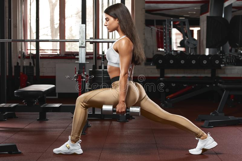 Fitness woman doing lunges exercises for leg muscle workout training. Active girl doing front forward one leg step lunge exercise.  stock image