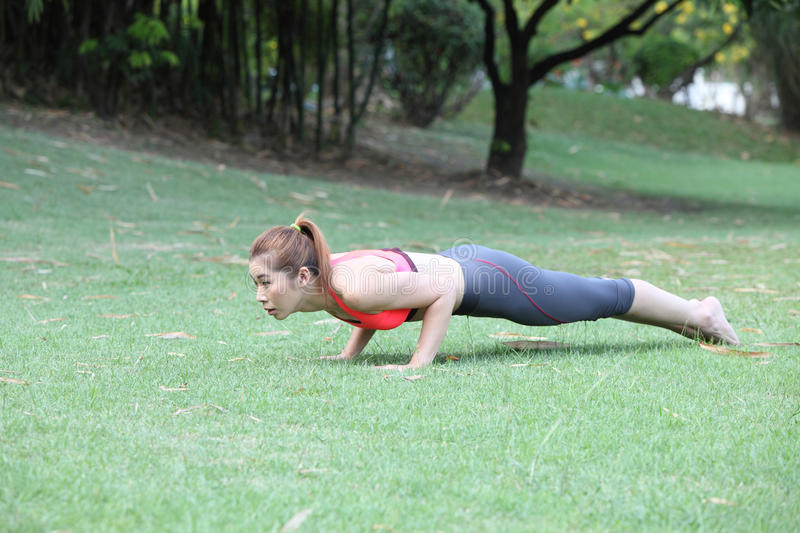 Fitness woman doing push-ups during outdoor cross training workout. Beautiful young and fit fitness sport model training outside royalty free stock image